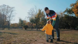 Portrait of happy young father and his son in autumn park. Slow motion. Playing with baby boy outdoor