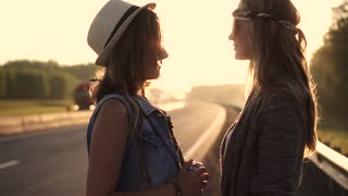 Portrait of two girls in hippie clothes at dawn. Girlfriends are sensually looking at each other