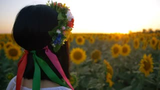 Portrait of young and beautiful woman in sunflower field on sunset. Lady in flower wreath. Slow motion. Freedom and carefree concept