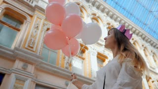 Portrait of Young happy woman with paper crown, colourful white and pink balloons smiling and laughing. Birthday girl in beautiful near old arhitecture. passage. Slow motion