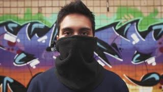 Portrait of young man graffiti artist on graffiti wall background, close up