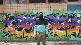 Portrait of young man graffiti artist on graffiti wall background