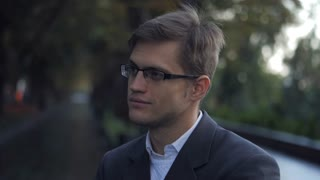 Portrait of young successful confident businessman in the city. Man in a business suit and glasses in the autumn street. Slow motion. Portrait of handsome guy
