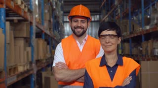 Portrait two workers in warehouse. Happy smiling professional Staff posing looking at the camera with friendly smile in logistic center. Young woman and handsome man wearing uniform high visibility