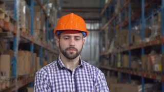 Portrait young professional worker posing looking at the camera. serious than smiling man at warehouse wearing uniform
