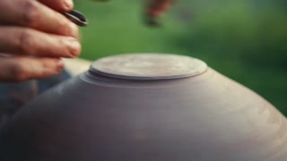 Potter shapes the bottom of the vessel via special tools. The process of creation. Professionalism, beautiful art, craft. Traditions, customs. Slow motion, camera stabilizer shot