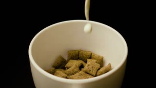 Pour the milk cereal pads chocolate in white bowl on black background slow motion