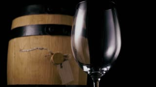 Pouring white wine into a glass in the background a wine barrel a black background. Slow mo