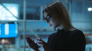 Pretty blonde-haired young woman in the glasses with black rim and dark clothes is on the evening street. She is near the business center. The girl is concentrated on her smartphone.