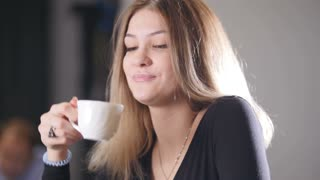 Pretty blonde young woman drinking coffee and smiling in the cafe