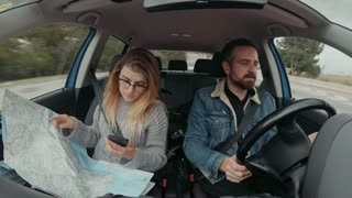 Pretty milennial hipster couple drives smal hybrid car during vacation or holiday. Woman holds vintage adventure paper map and uses smartphone gps navigation application to find location and address
