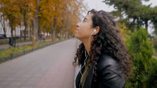 Pretty young hispanic girl with black curly long hair listening music in headphones on a deserted autumn street. Multi ethnic girl enjoying moment and singing. Slow motion