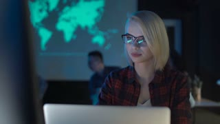 Pretty young woman working with laptop sitting in futuristic office