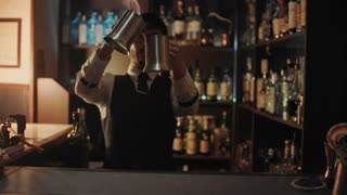 Professional bartender makes fire show mixing different alcohol drinks in big steel mugs and playing with flame pouring burning beverage from one cup to other in secret speak easy bar.