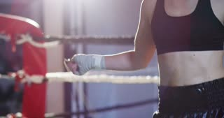 Professional boxer girl in the gym, jumping rope, improving stamina, speed and sharpness, excellent body and training, in black sportswear. Concept: love of sport, young boxers, love to win.