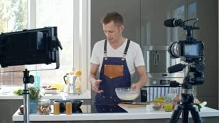 Professional chef in apron pouring creamy mixture into hot pan, then adding chopped spring onion and talking before digital camera while recording cooking show in kitchen