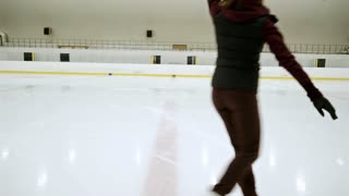 Professional female figure skater training for competition on indoor ice rink