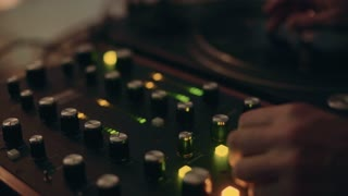 Professional sound engineer or dj, tweaks and adjusts controllers and buttons on turn mixing table to create strong powerful beat at live performance party or in studio
