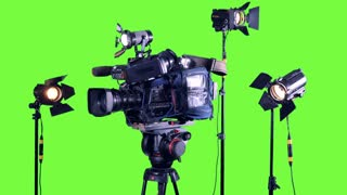 Professional studio spotlights and a professional video camera on a green screen.