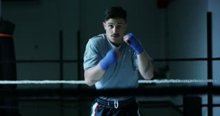 Professional young boxer in the ring, will practice the technique of strikes, struts, protection and endurance, blue eraser bandages, in camera. Concept: love of sport, young boxers, love of victory.