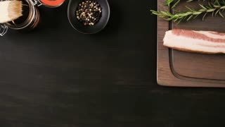 Raw bacon strips with fresh spices on a black ccutting board.