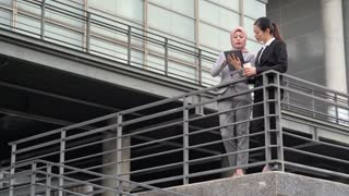 Muslim real estate manager using digital tablet explain to businesswoman