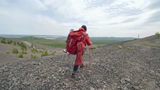 Rear view of female hiker walking with trekking poles on mountain top, standing and observing scenery view from above