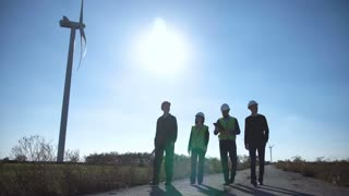 Rear view of four engineers walking along road at wind farm on sunny day