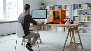 Rear view of male designer sitting at desk in the office and working with CAD software while creating 3D digital design on computer for 3D printer