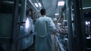 Rear wide view video of unrecognizable male scientist in white uniform walking through lad with metal tubes and engineering equipment aside
