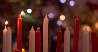 Red and white candles being lit in front of christmas decorations - slow motion