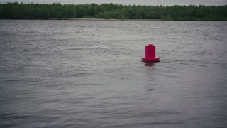 Red buoy on the river with a little excitement and on the other side of the forest and sky. Slow motion