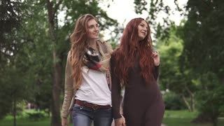 Red-haired girlfriends are walking in the park and holding hands. slow motion