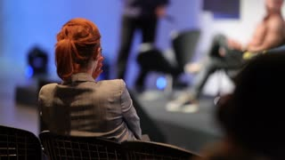 Red Head Woman From audience Listening To Speakers