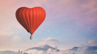 Red hot air balloon heart shape fly in blue and pink pastel sky. Foggy mountains in the background. Romantic journey on Valentine's Day. Travel, holidays, recreation. Nature landscape. Slow motion 4K