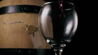 Red wine is poured into a wineglass against the background of a wine barrel. Black background. Slow motion