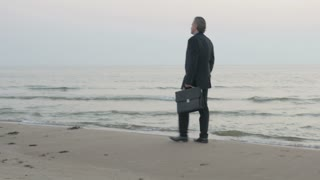 Sad mature businessman walking alone at the infinitive ocean. Man feeling depressed after being fired or finishing his career. Sad quiet shot.
