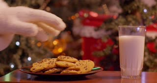 Santa dunking cookies in milk in front of the Christmas tree