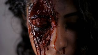 Scary portrait of young girl with Halloween blood makeup. Beautiful latin woman with curly hair looking into camera. Slow motion
