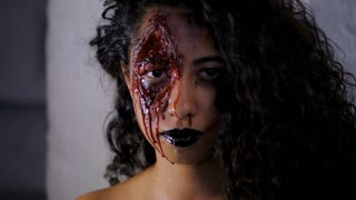 Scary portrait of young zombie girl with Halloween blood makeup. Beautiful latin woman with curly hair looking into camera in studio. Slow motion