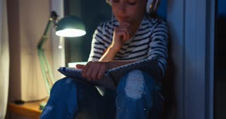 School Girl Writing In Exercise Book And Listening Music In Headphones Student Sitting On The Window Sill At Night