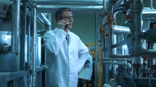Scientist in glasses and white lab coat standing among pipes and other factory equipment and talking on his phone