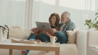 Senior couple with tablet relaxing at home.