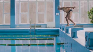 Senior man in an indoor swimming pool. Active pensioner enjoying sport. An old man jumping in the pool. Slow motion