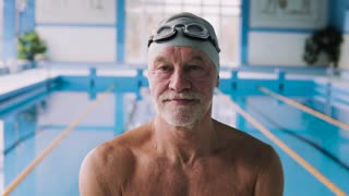 Senior man in an indoor swimming pool. Active pensioner enjoying sport