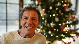 Senior man in front of illuminated Christmas tree.