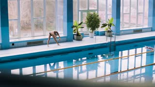 Senior man standing by the indoor swimming pool, stretching. Active pensioner enjoying sport
