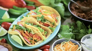 Serving ground beef tacos with romaine lettuce, diced tomatoes, radishes, and shredded cheddar cheese.