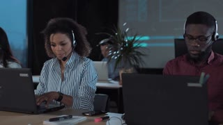 Several people with headsets in foreground working in call center in modern worldwide office, sitting in front of laptops at night or evening