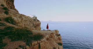 Shot from drone of petite blonde pretty girl ballerina dancing on edge of the cliff blissfully in romantic and happy way surrounded by ocean and mountains nature in calm peace, loving nature
